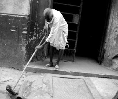 Woman cleaning in front of her home.  Photo: Caridad