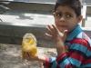 niño comiendo mango con aliños  en bulevar de catia