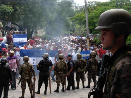 Soldiers and Police eye demonstrators at the Public Building.