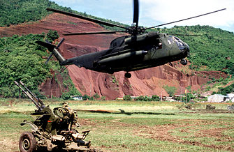 A Sikorsky CH-53D Sea Stallion helicopter of the U.S. Marine Corps hovers above the ground near an abandoned Soviet ZU-23-2 anti-aircraft weapon during the invasion of Grenada in 1983.