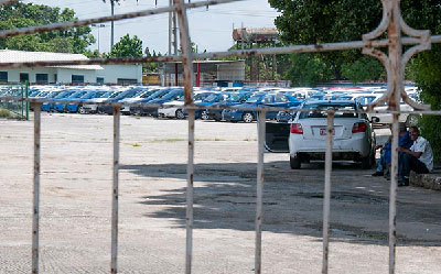 Hundreds of cars idle beneath the sun while people await an explanation as to why the sale of vehicles to Cubans has been suspended since the beginning of the year. Photo: Raquel Perez