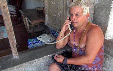 Adela's office in Cuba is a neighbor's porch, where there's a phone for public use.