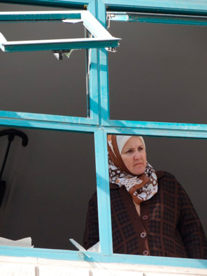 Woman looks out her broken window.  Photo/archivo: Julie Webb Pulman