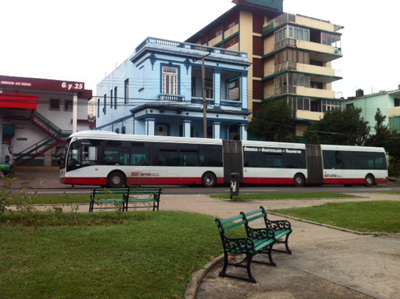 A three-car Metro Bus at its 25th and G St. stop in Vedado.