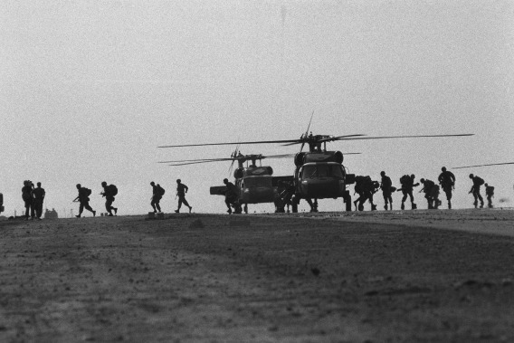 Troops are offloaded from US Army UH-60 Black Hawk helicopters onto the runway at Point Salines Airfield during the multiservice, multinational Operation URGENT FURY.