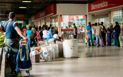 Shoppers waiting to get into a supermarket.  Buying basic products can  be an  all-day affair in Caracas.