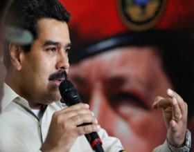 Venezuelan president Nicolas Maduro with a painting of former leader Hugo Chavez in the background.