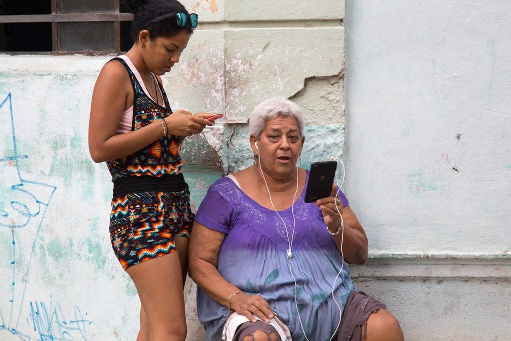 Different generations using the pay-for Wi-Fi in Havana.