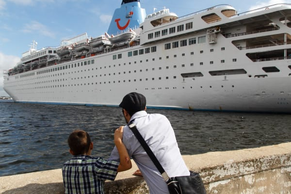 Father and son observe a cruiser in Havana Bay.
